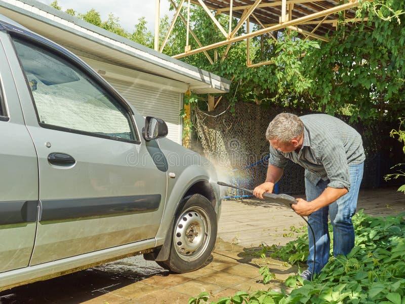 Άτομο που πλένει το ασημένιο αυτοκίνητό του κοντά στο σπίτι στοκ εικόνα