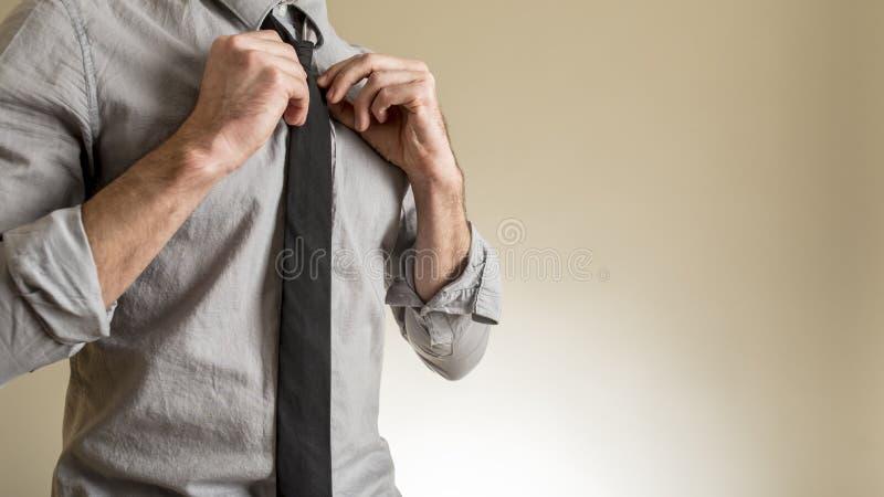Άτομο που ρυθμίζει τη μαύρη γραβάτα του στοκ φωτογραφίες με δικαίωμα ελεύθερης χρήσης