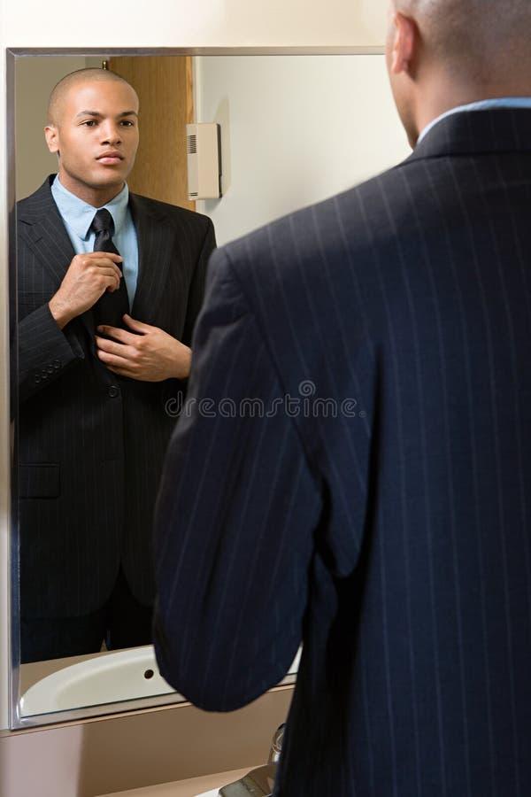 Άτομο που ρυθμίζει το δεσμό του στον καθρέφτη στοκ εικόνες
