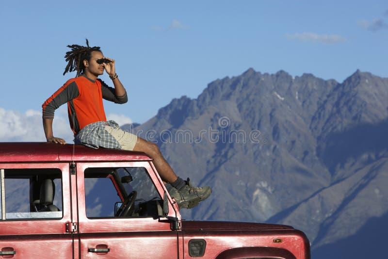 Άτομο που σκιάζει τα μάτια πάνω από το τζιπ κοντά στα βουνά στοκ εικόνες με δικαίωμα ελεύθερης χρήσης