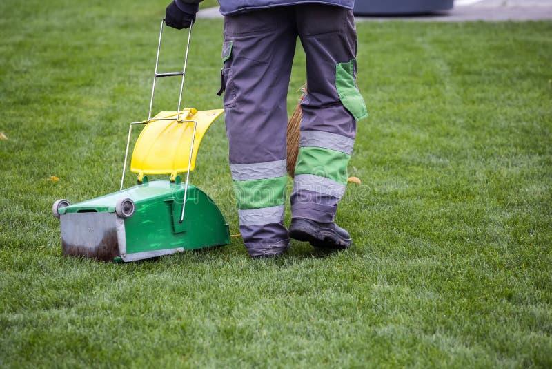 Άτομο που σκουπίζει τα πεσμένα ξηρά φύλλα φθινοπώρου στοκ φωτογραφία