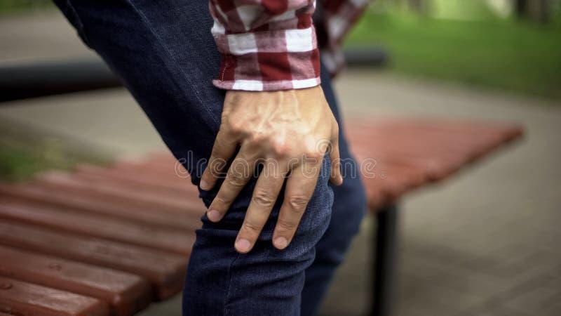 Άτομο που στέκεται επάνω από τον πάγκο που αισθάνεται τον αιχμηρό πόνο γονάτων, οστεοαρθρίτιδα, ζημία στοκ φωτογραφία με δικαίωμα ελεύθερης χρήσης
