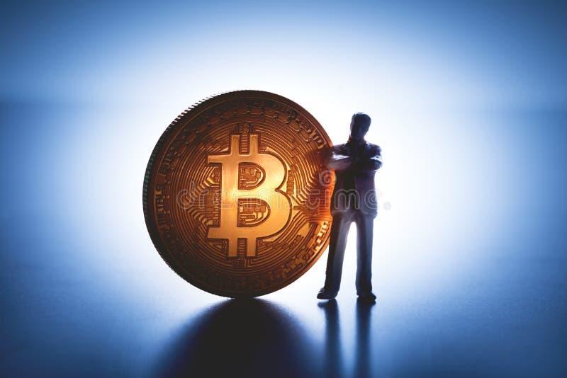 Άτομο που στέκεται με το μεγάλο νόμισμα bitcoin στοκ εικόνα με δικαίωμα ελεύθερης χρήσης