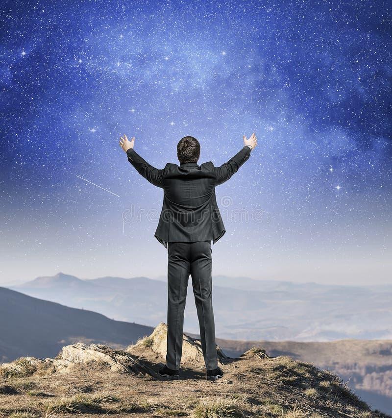 Άτομο που στέκεται πάνω από ένα βουνό σε ένα υπόβαθρο του νυχτερινού ουρανού στοκ φωτογραφία