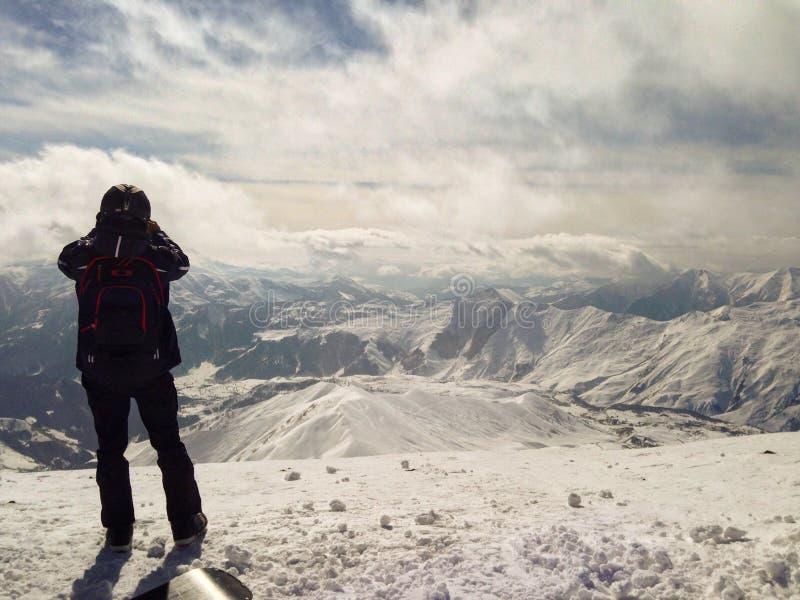 Άτομο που στέκεται πάνω από τα βουνά με τη μεγάλη άποψη του χιονώδους τοπίου Χειμερινό ταξίδι και έννοια περιπέτειας ακραίος αθλη στοκ εικόνες