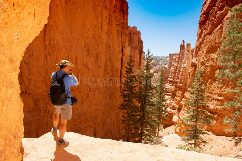 Άτομο που στέκεται πάνω από το βουνό που παίρνει τις φωτογραφίες με τη κάμερα του στοκ εικόνες