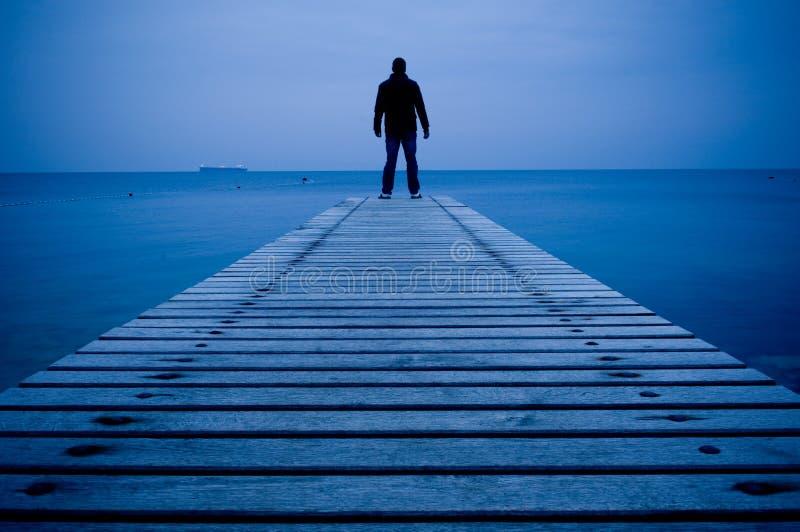 Άτομο που στέκεται σε μια ξύλινη αποβάθρα στοκ φωτογραφία