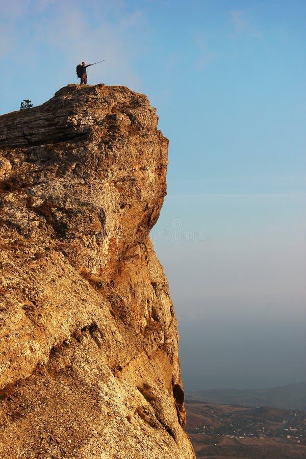 Άτομο που στέκεται στην άκρη του απότομου βράχου στοκ εικόνες