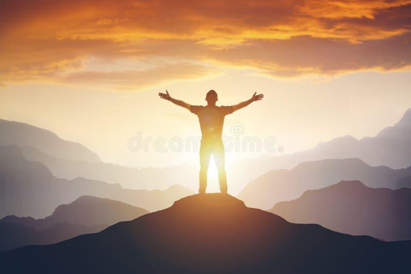 Άτομο που στέκεται στην άκρη του βουνού που αισθάνεται νικηφορόρη με τα όπλα επάνω στον αέρα στοκ εικόνες με δικαίωμα ελεύθερης χρήσης
