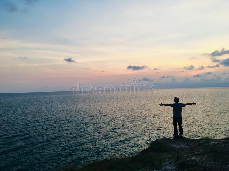Άτομο που στέκεται στον απότομο βράχο ακρών και που φαίνεται η θάλασσα στοκ εικόνα