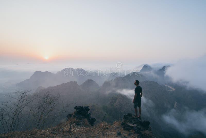 Άτομο που στέκεται στο βράχο που αγνοεί τα τροπικά βουνά στο ομιχλώδες πρωί ανατολής hpa-, το Μιανμάρ στοκ εικόνες
