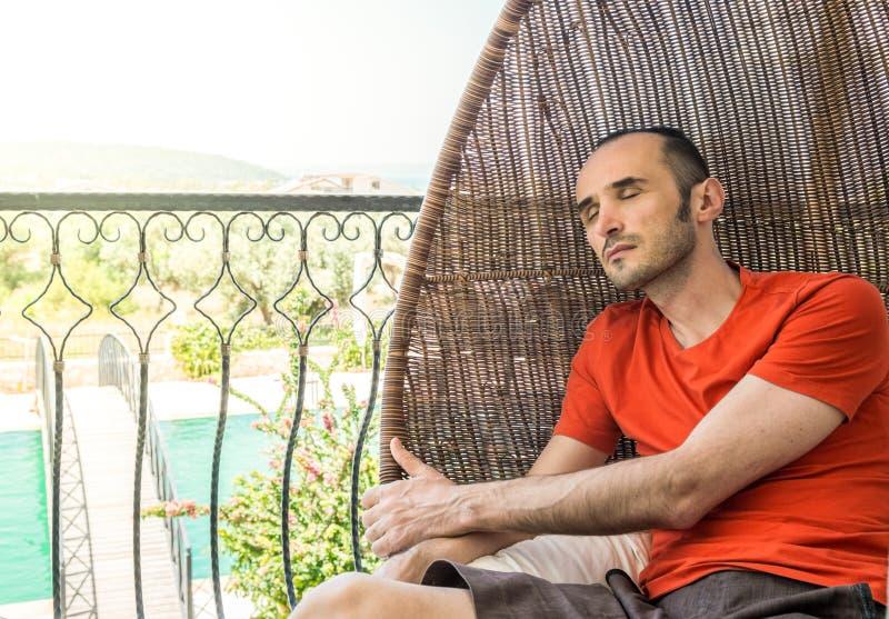 Άτομο που στηρίζεται για να χαλαρώσει στην ταλαντεμένος καρέκλα σε ένα μπαλκόνι στοκ φωτογραφία με δικαίωμα ελεύθερης χρήσης