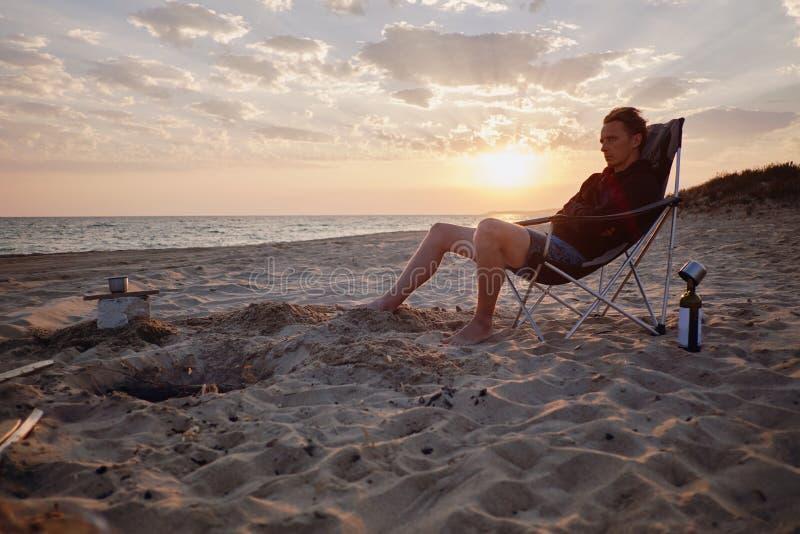 Άτομο που στηρίζεται στην παραλία άμμου στοκ εικόνα