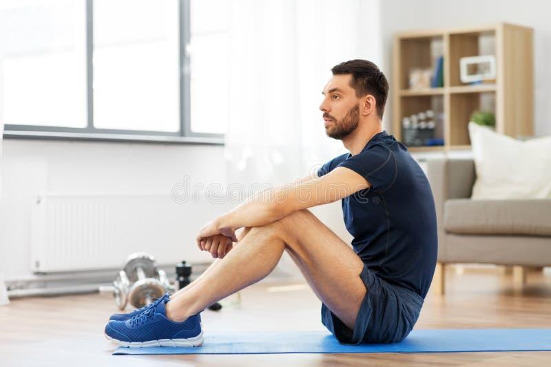Άτομο που στηρίζεται στο χαλί άσκησης στο σπίτι στοκ φωτογραφία