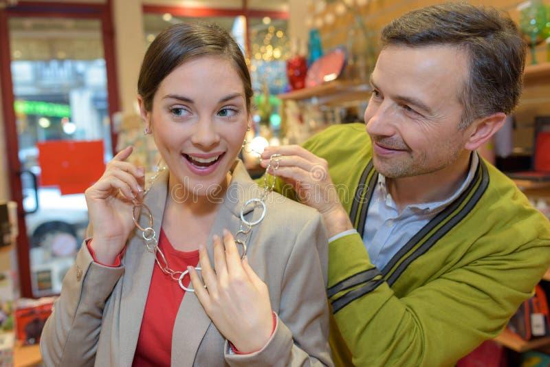 Άτομο που συνδέει το περιδέραιο με το λαιμό κοριτσιών στο μαγαζί λιανικής πώλησης στοκ εικόνες