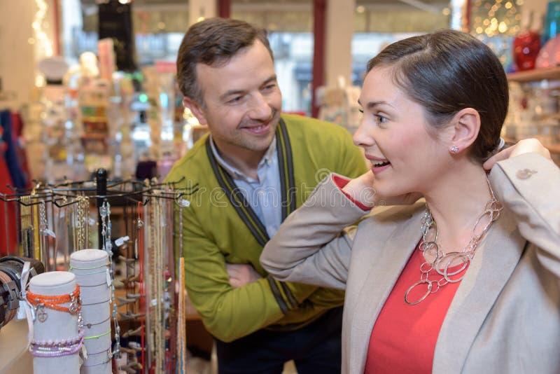 Άτομο που συνδέει το περιδέραιο με το λαιμό κοριτσιών στο μαγαζί λιανικής πώλησης στοκ εικόνες με δικαίωμα ελεύθερης χρήσης