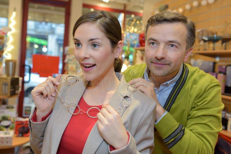 Άτομο που συνδέει το περιδέραιο με το λαιμό κοριτσιών στο μαγαζί λιανικής πώλησης στοκ εικόνα
