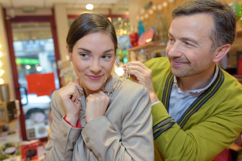 Άτομο που συνδέει το περιδέραιο με το λαιμό κοριτσιών στο μαγαζί λιανικής πώλησης στοκ φωτογραφίες