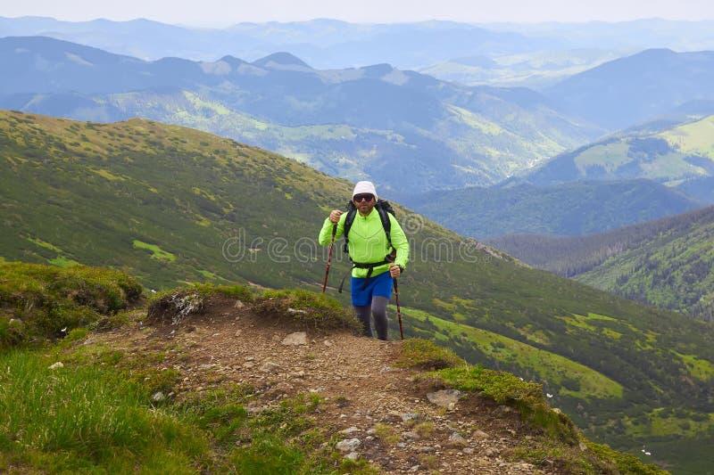 Άτομο που ταξιδεύει με το σακίδιο πλάτης που στις ενεργές διακοπές περιπέτειας έννοιας επιτυχίας τρόπου ζωής ταξιδιού βουνών υπαί στοκ εικόνα με δικαίωμα ελεύθερης χρήσης