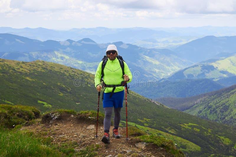 Άτομο που ταξιδεύει με το σακίδιο πλάτης που στις ενεργές διακοπές περιπέτειας έννοιας επιτυχίας τρόπου ζωής ταξιδιού βουνών υπαί στοκ φωτογραφία