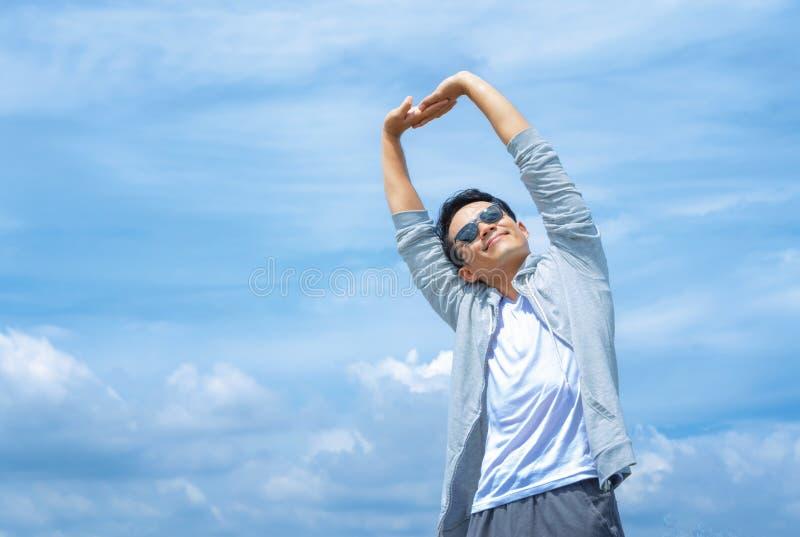 άτομο που τεντώνει τα όπλα του επάνω στο μπλε ουρανό στοκ εικόνες