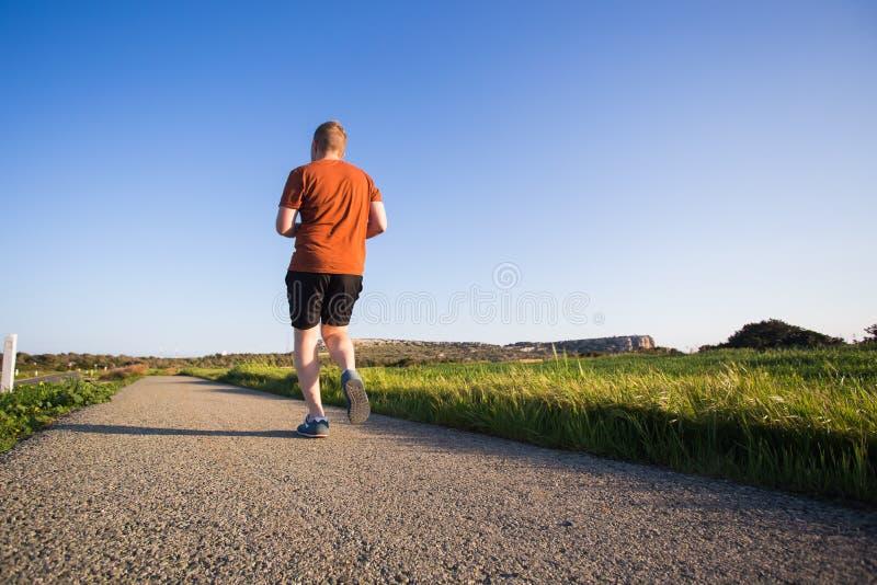 Άτομο που τρέχει υπαίθριο να τρέξει γρήγορα για την επιτυχία Αρσενικός αθλητικός αθλητής δρομέων ικανότητας στην ορμή με τη μεγάλ στοκ φωτογραφία