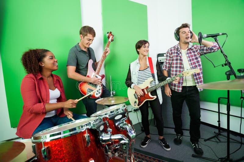 Άτομο που τραγουδά ενώ συνάδελφοι που παίζουν το μουσικό όργανο στοκ φωτογραφία με δικαίωμα ελεύθερης χρήσης