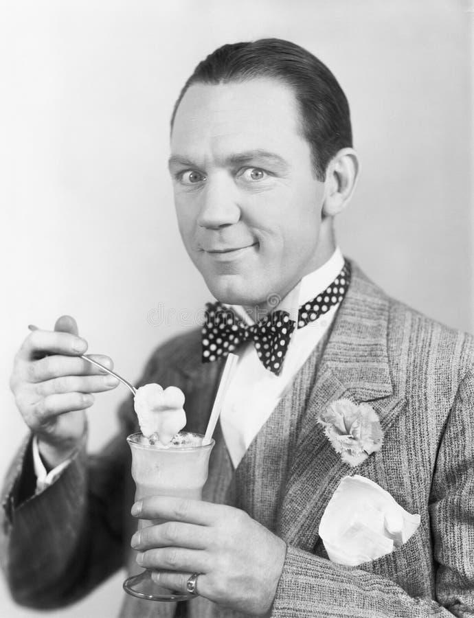Άτομο που τρώει ένα παγωτό από ένα γυαλί με ένα άχυρο (όλα τα πρόσωπα που απεικονίζονται δεν ζουν περισσότερο και κανένα κτήμα δε στοκ εικόνες