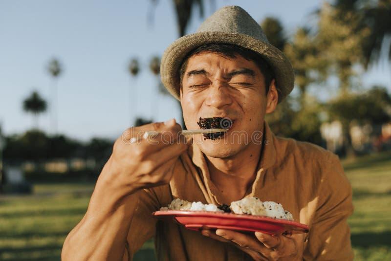 Άτομο που τρώει τα σούσια στο πάρκο στοκ φωτογραφία