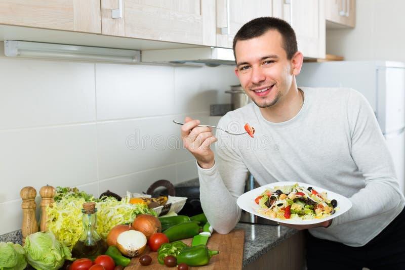 Άτομο που τρώει τη φυτική σαλάτα στην κουζίνα στοκ φωτογραφία με δικαίωμα ελεύθερης χρήσης