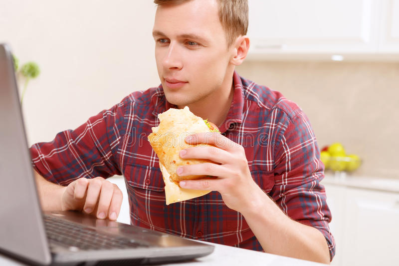 Άτομο που τρώει το σάντουιτς μπροστά από τον υπολογιστή στοκ εικόνες με δικαίωμα ελεύθερης χρήσης