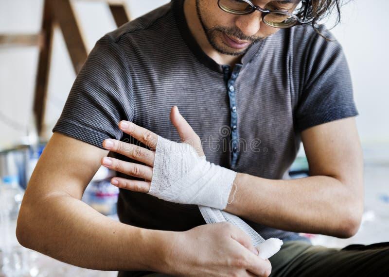 Άτομο που τυλίγει το τραυματισμένο χέρι με τον επίδεσμο στοκ εικόνα
