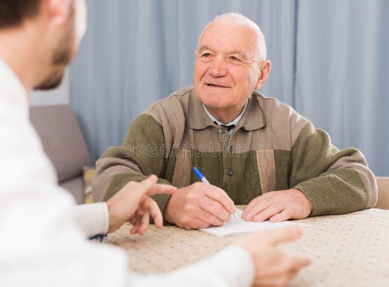 Άτομο που υπογράφει τα έγγραφα στο σπίτι στοκ φωτογραφία με δικαίωμα ελεύθερης χρήσης