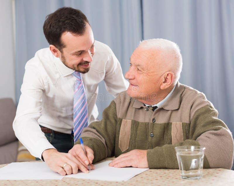 Άτομο που υπογράφει τα έγγραφα στο σπίτι στοκ εικόνα με δικαίωμα ελεύθερης χρήσης