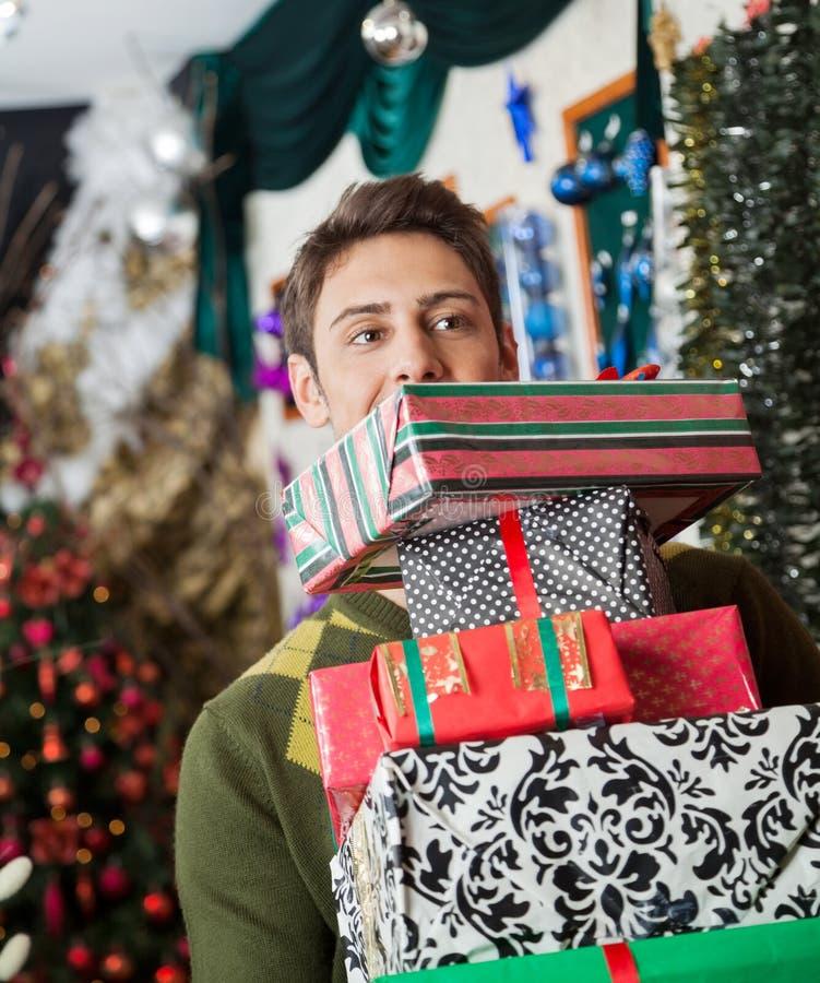 Άτομο που φέρνει τα συσσωρευμένα δώρα Χριστουγέννων στο κατάστημα στοκ φωτογραφίες