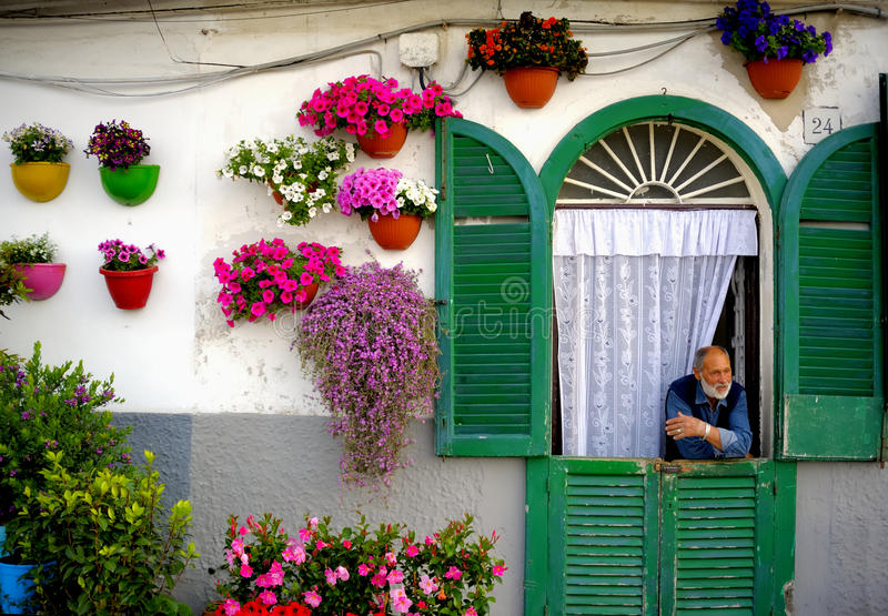 Άτομο που φαίνεται έξω η πόρτα του σπιτιού του με την πρόσοψη που διακοσμείται με τα ζωηρόχρωμα δοχεία λουλουδιών στοκ εικόνες