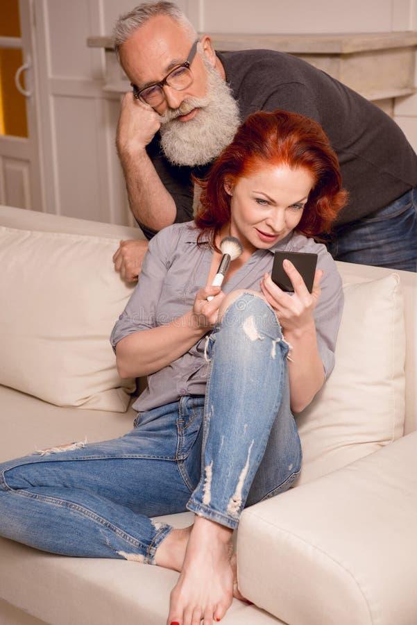Άτομο που φαίνεται πώς σύζυγος που ισχύει makeup στο σπίτι στοκ εικόνες