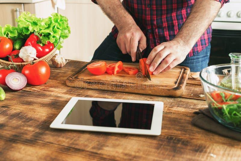 Άτομο που φαίνεται συνταγή στην ψηφιακή ταμπλέτα και τα μαγειρεύοντας υγιή τρόφιμα στοκ φωτογραφία με δικαίωμα ελεύθερης χρήσης
