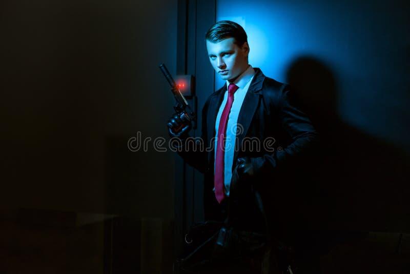 Άτομο που φορά τα γάντια και με ένα πυροβόλο όπλο στοκ φωτογραφίες
