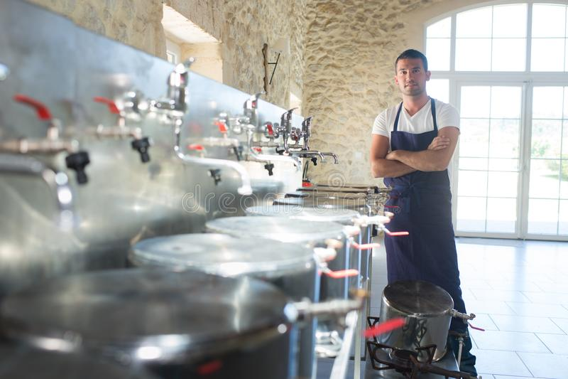 Άτομο που φορά την ομοιόμορφη στάση μεταξύ του ανοξείδωτου εξοπλισμού ζυθοποιείων στοκ φωτογραφία με δικαίωμα ελεύθερης χρήσης