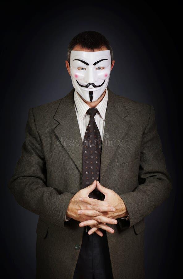 Άτομο που φορά τις ανώνυμες στάσεις μασκών στο σκοτεινό κλίμα στοκ φωτογραφία με δικαίωμα ελεύθερης χρήσης