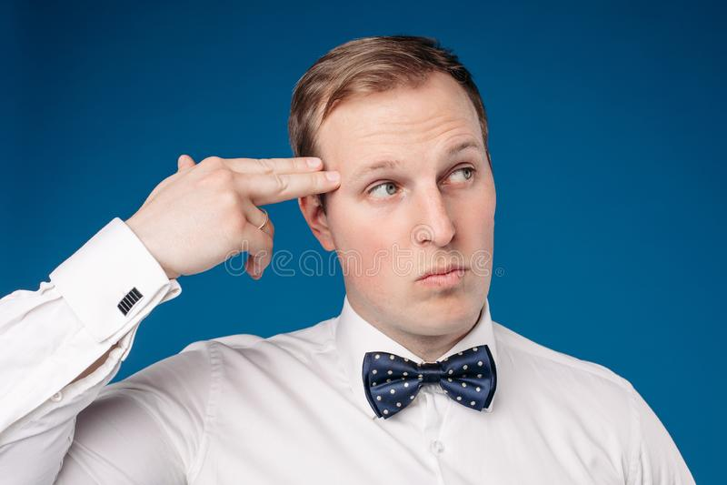Άτομο που φορά τον άσπρο δεσμό πουκάμισων και τόξων που παρουσιάζει σημάδι του πιστολιού στοκ εικόνα με δικαίωμα ελεύθερης χρήσης