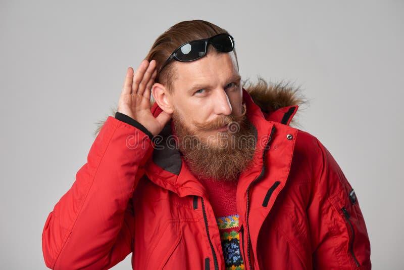 Άτομο που φορά το κόκκινο χειμερινό σακάκι με το χέρι στο αυτί στοκ φωτογραφία με δικαίωμα ελεύθερης χρήσης