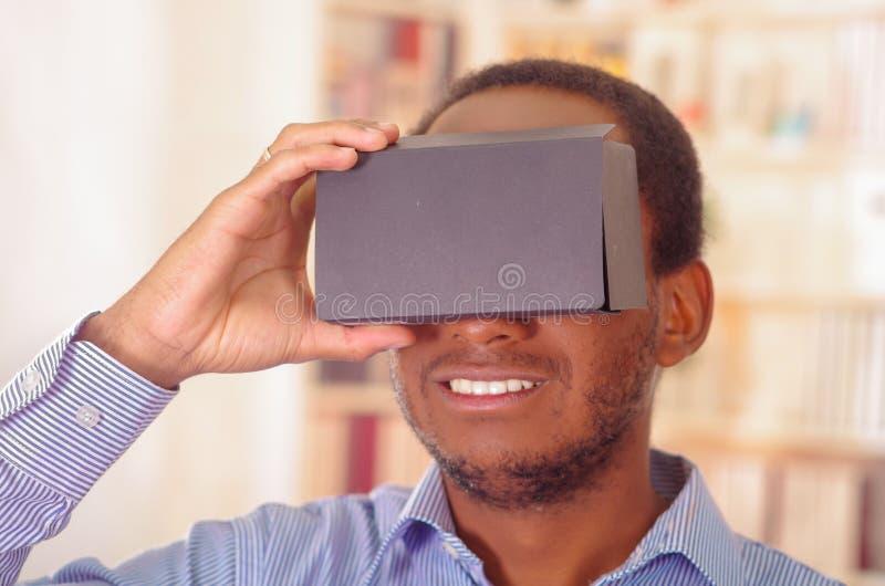 Άτομο που φορά το μπλε πουκάμισο που εξετάζει τη vitrual συσκευή, το κράτημα των γυαλιών μπροστά από τα μάτια και το χαμόγελο πρα στοκ εικόνες με δικαίωμα ελεύθερης χρήσης