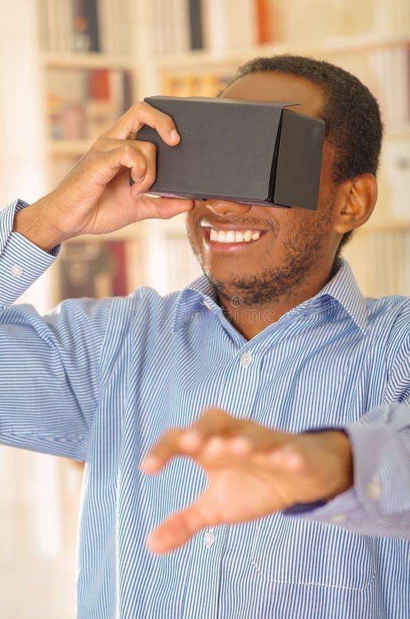 Άτομο που φορά το μπλε πουκάμισο που εξετάζει τη vitrual συσκευή, το κράτημα των γυαλιών μπροστά από τα μάτια και το χαμόγελο πρα στοκ φωτογραφία