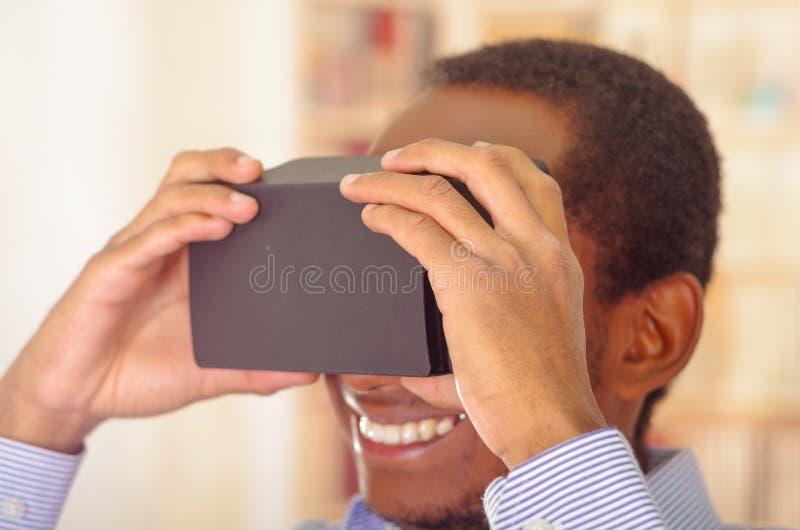 Άτομο που φορά το μπλε πουκάμισο που εξετάζει τη vitrual συσκευή, το κράτημα των γυαλιών μπροστά από τα μάτια και το χαμόγελο πρα στοκ φωτογραφία με δικαίωμα ελεύθερης χρήσης