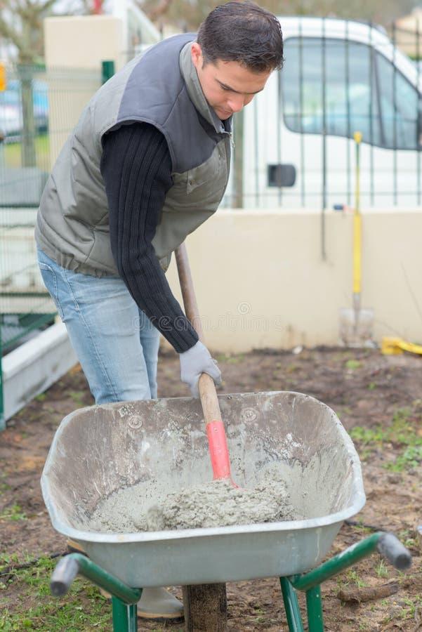 Άτομο που φτυαρίζει το τσιμέντο wheelbarrow στο εργοτάξιο οικοδομής σπιτιών στοκ εικόνες