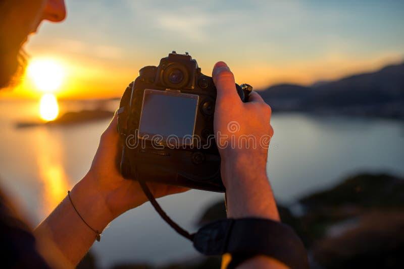 Άτομο που φωτογραφίζει το ηλιοβασίλεμα στην κορυφή του βουνού στοκ εικόνα