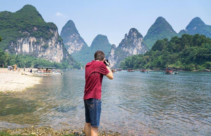 Άτομο που φωτογραφίζει το τοπίο του ποταμού λι σε Yangshuo Κίνα στοκ εικόνες