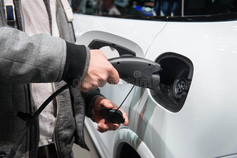 Άτομο που χρεώνει το ηλεκτρο αυτοκίνητο Άτομο που κρατά το διαθέσιμο ανεφοδιασμό καλωδίου τροφοδοσίας χεριών έτοιμο συνδεμένος με στοκ φωτογραφίες